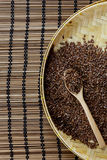 Flax seed with spoon placed on flat woven basket. Royalty Free Stock Image