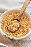 Flax seed on a wooden spoon in an old bowl on a wooden table Stock Photography