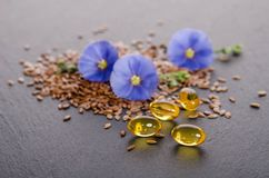 Flax seeds, beauty flower and oil in caps on a grey background Stock Photos
