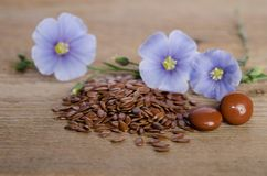 Flax seeds, beauty flower and pills on woooden background Stock Photos