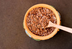 Flax seeds in a bowl with wooden spoon, selective focus Royalty Free Stock Photography