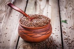 Flax seeds in bowl on a wooden table Stock Photos