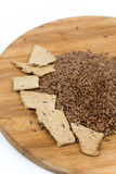 Flax seeds with flax snacks on the board Royalty Free Stock Photography