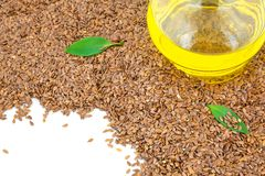 Flax seeds and glass bottle of oil with green leaves Stock Photo
