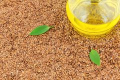Flax seeds and glass bottle of oil with leaves Stock Image