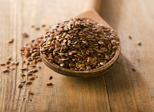 Flax seeds heap on a wooden spoon Royalty Free Stock Images