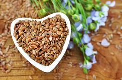 Flax seeds in heart-shaped bowl and blue linum plants stock photos