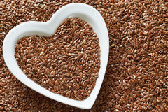 Flax seeds in heart shaped ceramic bowl Royalty Free Stock Photography