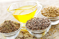 Flax seeds and linseed oil. Bowls of whole and ground flax seed with linseed oil stock images