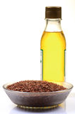 Flax seeds and oil. Bowl of flax seeds and oil bottle isolated on white background Royalty Free Stock Images