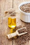 Flax seeds and oil in bottle on wooden background stock photo
