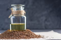 Flax seeds in a pile and linseed golden oil in a glass bottle. Concept healthy diet with omega 3 fatty acids. Flax seeds in a pile and linseed golden oil in a stock images