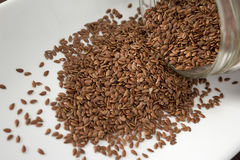 Flax seeds spilling out of container, close up Stock Photography