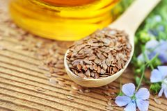 Flax seeds in spoon. With linseeds and linum plants, wooden background stock images