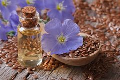 Flax seeds in a spoon and oil in a bottle close-up horizontal Royalty Free Stock Photo