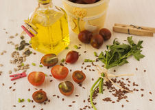 Flax seeds, tomatoes cherry and oil in bottle. Flax seeds, tomatoes cherry and oil in bottle on wooden background Stock Images