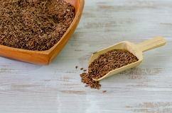Flax seeds in wooden bowl and wooden spoon royalty free stock photo