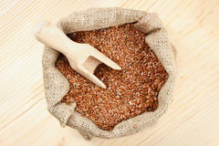 Flax seeds with wooden scoop in sack Stock Images