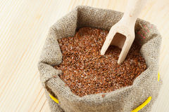 Flax seeds with wooden scoop in sack Royalty Free Stock Image