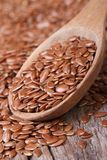 Flax seeds in a wooden spoon macro. Vertical Stock Photos