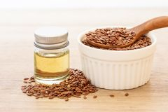 Flaxseed essential oil and seeds in wooden spoon , Heart healt royalty free stock image