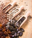 Flaxseed, pumpkin, raisins, lentils and sunflower seeds in wooden spoons. Royalty Free Stock Images