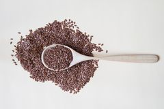 Flaxseeds on wooden spoon on beige background Top view. Royalty Free Stock Image