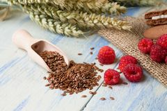 Flaxseeds in wooden spoon next to raspberries Royalty Free Stock Photo