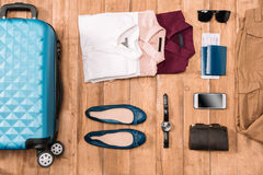Flay lay of business holiday concept with clothes, digital gadgets, passport and tickets. On wooden floor Stock Images