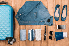 Flay lay of business holiday concept with clothes, smartphone, passport and tickets. On wooden floor Royalty Free Stock Photo