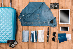 Flay lay of business holiday concept with clothes, smartphone, passport and tickets. On wooden floor Stock Photography