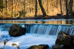 Flödande blått vatten under den varma orange Wiinter skogen Arkivfoto