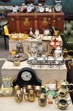 Flea market. Old table silver, clocks and other stuff in a flea market royalty free stock photo