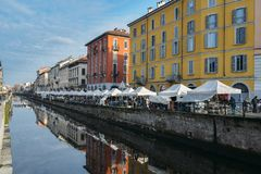 Flea market along the Naviglio Grande canal in bohemian Navigli district of Milan, Italy. The canal is 50km long. Milan, Italy - Feb 24, 2018: Flea market along royalty free stock image