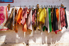 Flea market in India. Colorful t-shirts and pants are shown on a white wall of the shop at the flea market in India royalty free stock photo