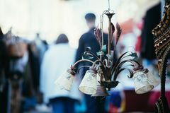Flea market: Old fashioned lamp in the foreground, people in the blurry background. Old fashioned lamp on a flea market, people in the blurry background sale stock photo