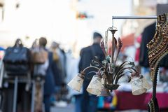 Flea market: Old fashioned lamp in the foreground, people in the blurry background. Old fashioned lamp on a flea market, people in the blurry background sale royalty free stock images