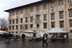 Flea market and Palazzo della Carovana at the Knights Square in royalty free stock images