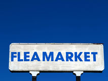 Flea Market Sign. White flea market sign with bold blue lettering and brilliant blue sky in the background royalty free stock photography