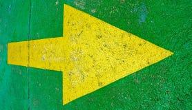 Flecha amarilla grande que señala a la derecha con el fondo verde Imágenes de archivo libres de regalías