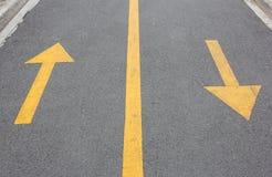Flecha amarilla hacia arriba y hacia abajo en la calle del asfalto Fotos de archivo