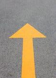 Flecha amarilla para arriba en la calle del asfalto Imagen de archivo