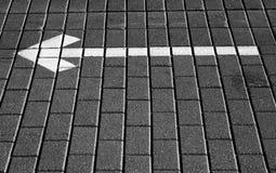 Flecha blanca con la dirección izquierda en el pavimento de la piedra del adoquín Imagen de archivo libre de regalías
