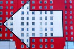 Flecha blanca izquierda en el edificio rojo Foto de archivo libre de regalías