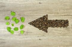Flecha de los granos de café con el fondo de madera de la hoja de té de la menta Fotos de archivo