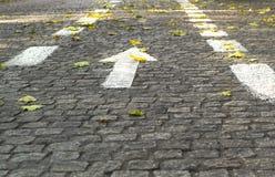 Flecha direccional blanca en el pavimento de piedra Foto de archivo libre de regalías
