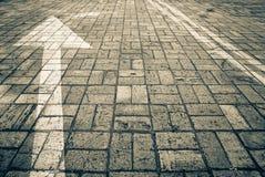 Flecha direccional y dos líneas continuas pintadas en el camino pavimentado imagen de archivo