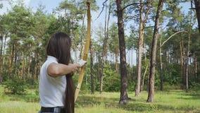 Flecha draving del arquero de sexo femenino y blanco que tira almacen de metraje de vídeo
