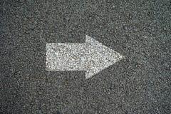 Flecha en encendido las carreteras de asfalto Foto de archivo libre de regalías