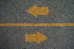 Flecha enfrente de direcciones en encendido las carreteras de asfalto Imagen de archivo libre de regalías